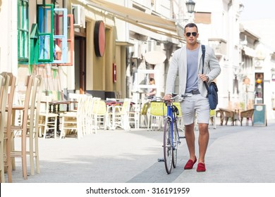 Handsome young man walking down the street with his bicycle beside him