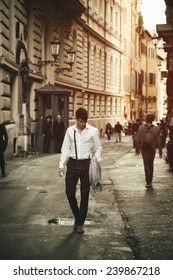Handsome young man walking in European city street, an alley in Rome, Italy
