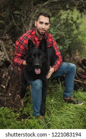 Handsome young man walking in the forest with his dog, selective focus
