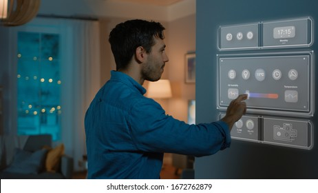 Handsome Young Man Walks Over to a Refrigerator. He is Changing Temperature on Smart Fridge Screen at Home. Cozy Kitchen Evening.