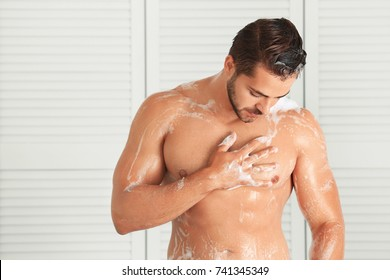 Handsome young man washing in shower