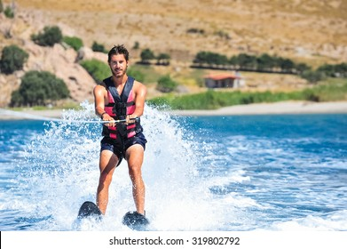 Handsome young man waterskiing on the sea. Happy man on holiday doing water sports and having fun. Holiday abroad on an island.