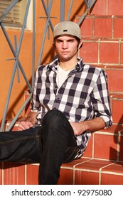 Handsome young man wearing baseball cap outdoors in urban setting.