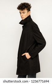 Handsome young man wearing black long trench coat