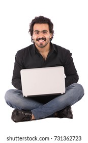 Handsome young man wearing black shirt and jeans with a laptop, guy sitting on the floor and smiling, isolated on white background
