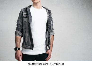 Handsome young man wearing blank t-shirt and jacket, white bricks wall background. Studio portrait