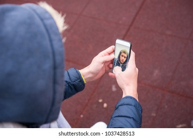 Handsome young man, wearing blue hoodie taking selfie with mobile phone