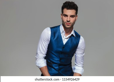 handsome young man wearing a blue waistcoat while sitting on a grey background, portrait picture