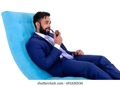 Handsome young man wearing a blue suit sitting in armchair smoking pipe and enjoying life, isolated on white