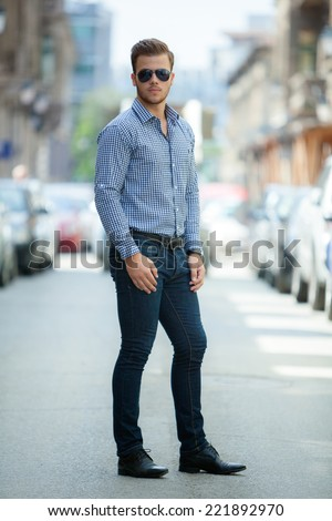 398a65f9b35 Handsome young man wearing a blue shirt and jeans. Street shooting in  Timisoara