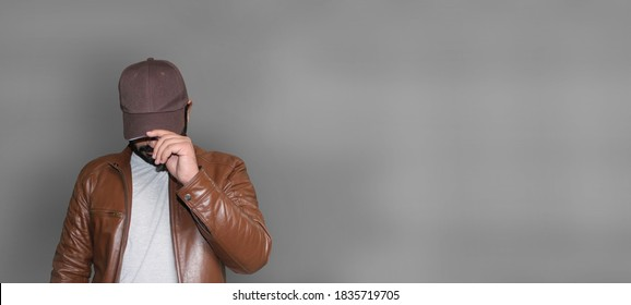 Handsome young man wearing brown leather jacket hiding his face behind the Cap.