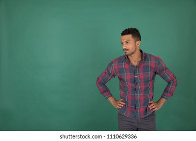 Handsome young man wearing a casual outfit, putting his hands in his waist waiting for something, looking upset, standing on a green background.