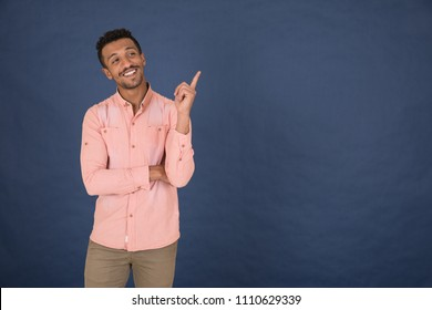 Handsome young man wearing a casual outfit, he is got a good idea pointing with his finger up, standing on a navy background