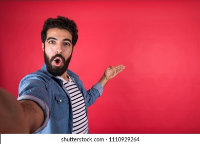 Handsome young man wearing a casual outfit taking a selfie by his phone, looking so excited, standing on a red background.