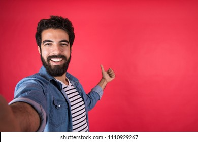 Handsome young man wearing a casual outfit taking a selfie by his phone, raising his thumb up, standing on a red background.