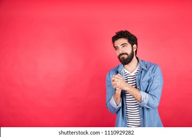 Handsome young man wearing a casual outfit seems that he is apologizing and want to say sorry, standing on a red background.