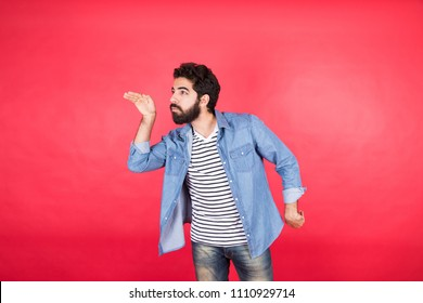 Handsome young man wearing a casual outfit, dancing with silly moves, looking so funny, standing on a red background.