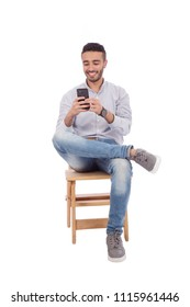 Handsome young man wearing a casual outfit, sitting crossed legs on a wood chair and holding his phone chatting with his friend, isolated on white background.