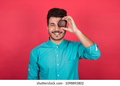 Handsome young man wearing a classic outfit, holding a chocolate biscuits putting it on his eye looking very funny, standing on a red background.