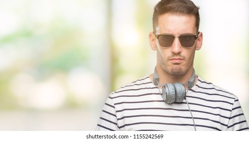 Handsome young man wearing headphones skeptic and nervous, frowning upset because of problem. Negative person.