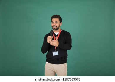 Handsome young man wearing his ID and holding a mic and speak and seems that he is arguing with someone and laughing, Standing on a green background.