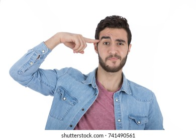 Handsome young man wearing jeans shirt and black pants, guy pointing to his head, isolated on white background