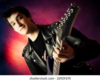 handsome young man wearing a leather jacket playing a guitar