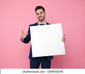 handsome young man wearing navy blue suit, holding an empty board and pointing finger, standing on pink background in studio
