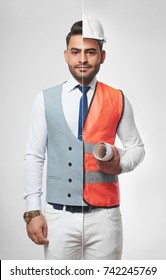 Handsome young man wearing smart casual business outfit and safety vest with a hardhat carrying a blueprint profession occupation job career architecture constructionist success CEO.