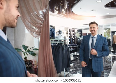 Handsome young man wearing suit looking in mirror at store