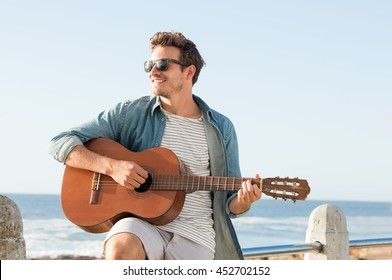 Handsome young man wearing sunglasses and playing guitar on fence near beach. Smiling guy playing acoustic guitar at sunset. Carefree man looking away at sea shore.