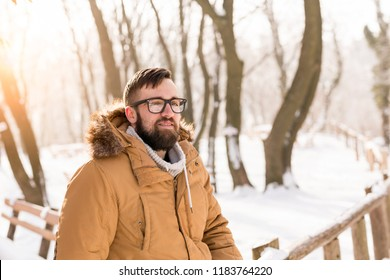 Handsome young man wearing a warm winter clothes, leaning against a wooden fence and enjoying a snowy winter day in the mountains