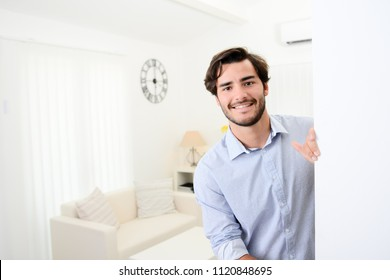 handsome young man welcome friends at open front door new student home apartment