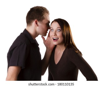 Handsome young man whispers to the beautiful young brunette isolated on white background
