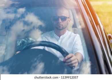 Handsome young man in white shirt and sunglasses driving a car without seat belt. Traffic law violation. Window reflecting sky, natural lighting, no retouch, matte filter.