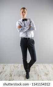Handsome young man in white shirt and bow tie poses in grey studio, full body
