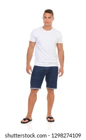 Handsome young man in white shirt, jeans shorts and black sandals is standing and looking at camera. Front view. Full length studio shot isolated on white.