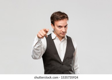 Handsome young man in a white shirt and grey vest pointing his finger at the camera isolated over grey background.