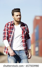 Handsome young man in white t shirt, shirt and jeans outdoors