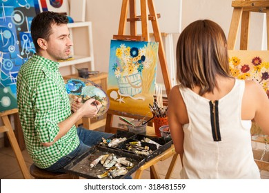 Handsome young man and women comparing their paintings while studying at an art school