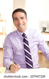 A handsome young man at work with a big smile looking at camera with a pen wearing purple shirt and tie