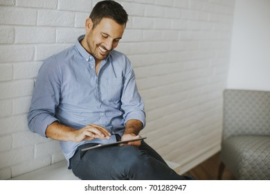 Handsome young man working with digital tablet in the room