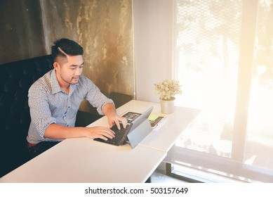 Handsome Young man working on laptop while sitting at his working place at work