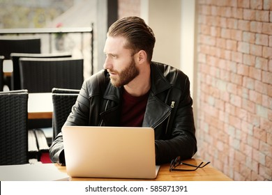 Handsome young man working on laptop at cafe
