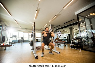 Handsome young man working out with barbells in the gym