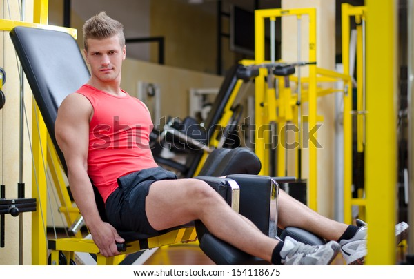 Handsome young man working out, exercising legs on gym equipment