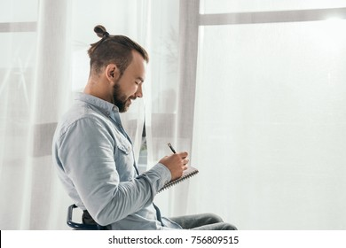 handsome young man writing in notebook in front of window
