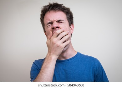 Handsome young man yawning with eyes shut and hand covers mouth. Wears blue t-shirt against white background.