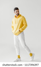 handsome young man in yellow hoodie posing on white
