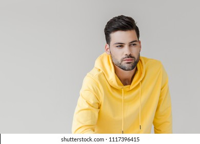 handsome young man in yellow hoodie looking away isolated on white